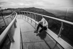 Hombre joven que se sienta en las montañas Esperanza tristeza Libertad Foto de archivo libre de regalías