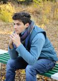 Hombre joven que se sienta en parque. Imagen de archivo