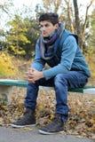 Hombre joven que se sienta en parque. Imagen de archivo libre de regalías