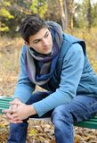 Hombre joven que se sienta en parque. Fotografía de archivo