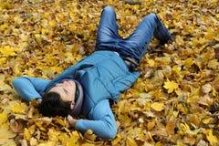 Hombre joven que se sienta en parque. Fotos de archivo
