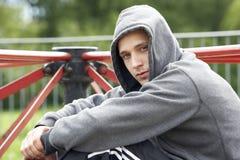 Hombre joven que se sienta en patio Fotografía de archivo
