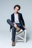 Hombre joven que se sienta en silla foto de archivo