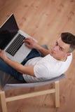 Hombre joven que se sienta en silla con el ordenador portátil Imagen de archivo