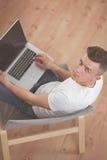 Hombre joven que se sienta en silla con el ordenador portátil Fotografía de archivo libre de regalías