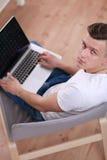 Hombre joven que se sienta en silla con el ordenador portátil Fotos de archivo libres de regalías
