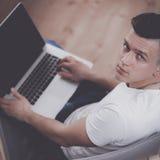 Hombre joven que se sienta en silla con el ordenador portátil Foto de archivo