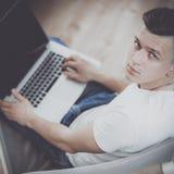 Hombre joven que se sienta en silla con el ordenador portátil Imagen de archivo libre de regalías
