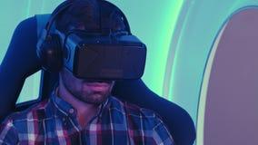 Hombre joven que se sienta en silla interactiva de la realidad virtual Imagen de archivo