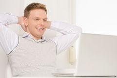 Hombre joven que se sienta en silla y la sonrisa Fotografía de archivo
