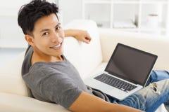 Hombre joven que se sienta en sofá y que usa el ordenador portátil Imagenes de archivo