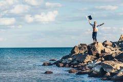 Hombre joven que se sienta en un anuncio de la roca usando el ordenador portátil Fotos de archivo