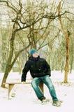 Hombre joven que se sienta en un banco Fotos de archivo