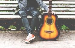 Hombre joven que se sienta en un banco con una guitarra Foto de archivo libre de regalías