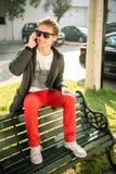 Hombre joven que se sienta en un banco que habla en el teléfono Imagen de archivo