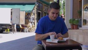 Hombre joven que se sienta en un café asiático tradicional metrajes