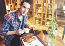 Hombre joven que se sienta en un café, usando una tableta Foto de archivo