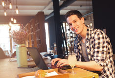 Hombre joven que se sienta en un café, usando un ordenador portátil Fotografía de archivo libre de regalías