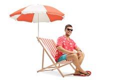 Hombre joven que se sienta en un deckchair debajo de un paraguas y que sonríe en la cámara imagen de archivo