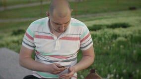 Hombre joven que se sienta en un parque de la ciudad que mira en su bolso para su teléfono almacen de metraje de vídeo