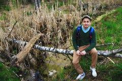 Hombre joven que se sienta en un tronco de árbol caido entre los árboles que disfrutan de la naturaleza Imagen de archivo libre de regalías