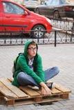 Hombre joven que se sienta en una acera Imagen de archivo