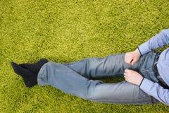 Hombre joven que se sienta en una alfombra Foto de archivo libre de regalías
