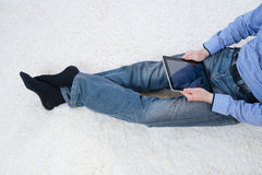 Hombre joven que se sienta en una alfombra con la tableta Imagen de archivo