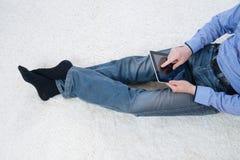 Hombre joven que se sienta en una alfombra con la tableta Fotos de archivo