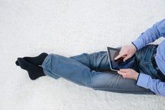 Hombre joven que se sienta en una alfombra con la tableta Fotos de archivo libres de regalías