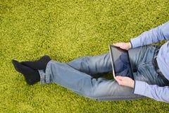 Hombre joven que se sienta en una alfombra con la tableta Imagenes de archivo