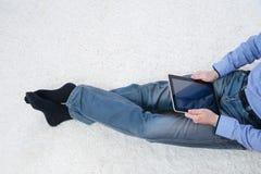 Hombre joven que se sienta en una alfombra con la tableta Imágenes de archivo libres de regalías