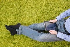 Hombre joven que se sienta en una alfombra con la tableta Imagen de archivo libre de regalías
