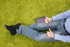 Hombre joven que se sienta en una alfombra con la tableta Foto de archivo