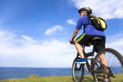 Hombre joven que se sienta en una bici de montaña y que mira el océano Imagen de archivo libre de regalías
