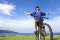 Hombre joven que se sienta en una bici de montaña y brazos abiertos a la relajación Imagen de archivo