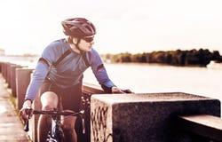 Hombre joven que se sienta en una bicicleta Imágenes de archivo libres de regalías