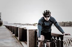 Hombre joven que se sienta en una bicicleta Imagen de archivo libre de regalías
