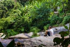 Hombre joven que se sienta en una cascada en la selva de Chiang Mai imagenes de archivo