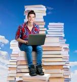 Hombre joven que se sienta en una pila de libros con un ordenador portátil Imagen de archivo