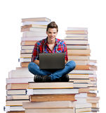 Hombre joven que se sienta en una pila de libros con un ordenador portátil Fotografía de archivo libre de regalías