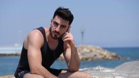 Hombre joven que se sienta en una playa sola y sola almacen de video