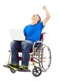 Hombre joven que se sienta en una silla de ruedas y excitado para aumentar el brazo Imagen de archivo libre de regalías