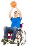 Hombre joven que se sienta en una silla de ruedas y que lleva a cabo un baloncesto Fotografía de archivo libre de regalías
