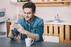 Hombre joven que se sienta en una tabla en la cocina con su teléfono móvil Fotos de archivo