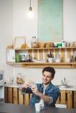 Hombre joven que se sienta en una tabla en la cocina con su teléfono móvil Imagenes de archivo
