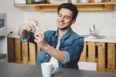Hombre joven que se sienta en una tabla en la cocina con su teléfono móvil Fotos de archivo libres de regalías