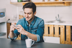 Hombre joven que se sienta en una tabla en la cocina con su teléfono móvil Imagen de archivo libre de regalías