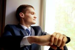 Hombre joven que se sienta en windowsill Imágenes de archivo libres de regalías