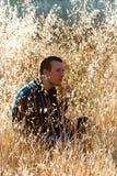 Hombre joven que se sienta entre las hierbas fotografía de archivo libre de regalías